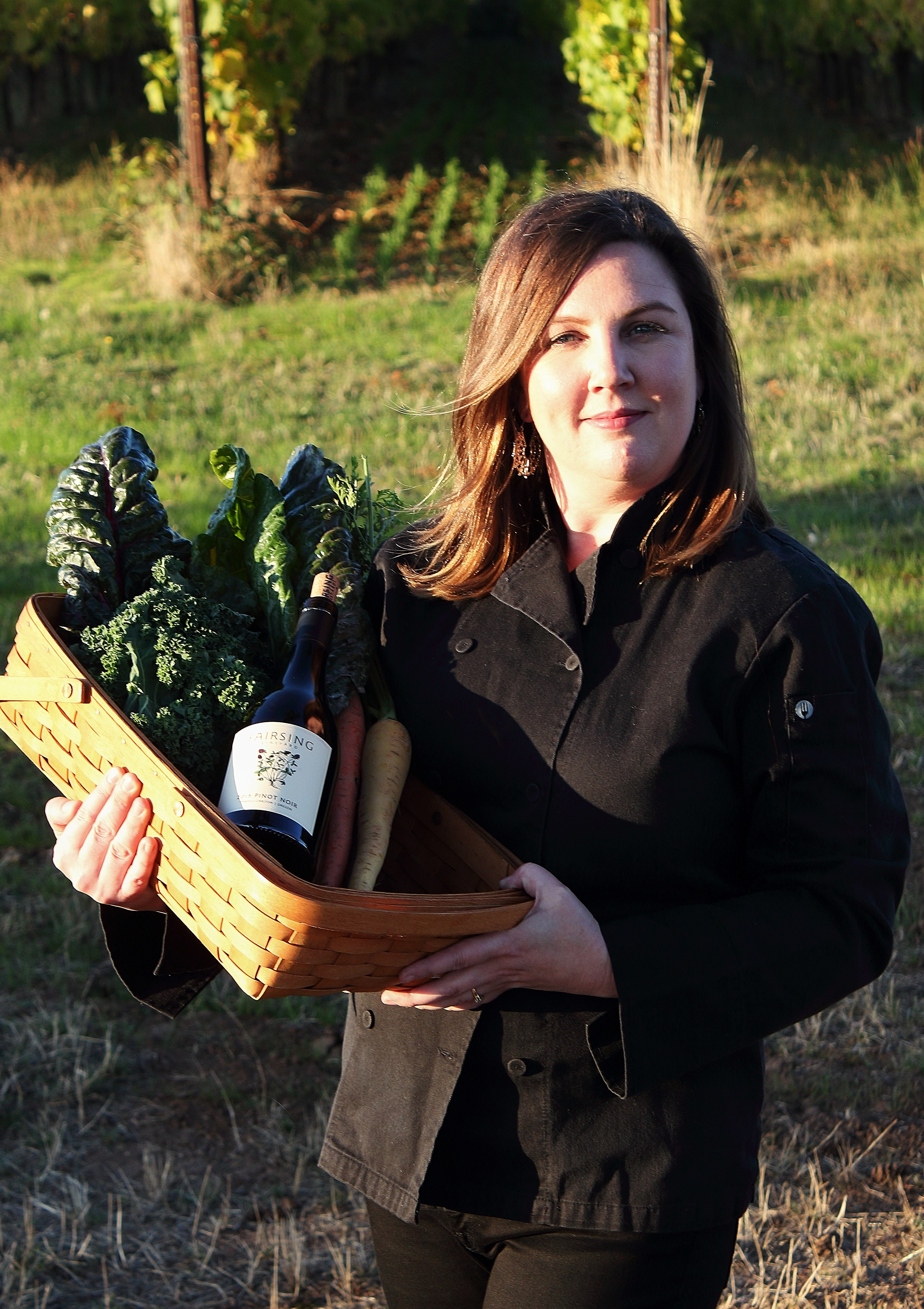 Fairsing Vineyard Chef Rebecca Clarke in the vineyard with wine and harvested produce