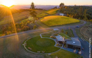 "High above the Fairsing Vineyard tasting room and meditative labyrinth as the sun sets behind the Coastal Mountain Range in Oregon's Willamette Valley as featured in the 1859 Oregon's Magazine March edition article ""Libation Vacation""."