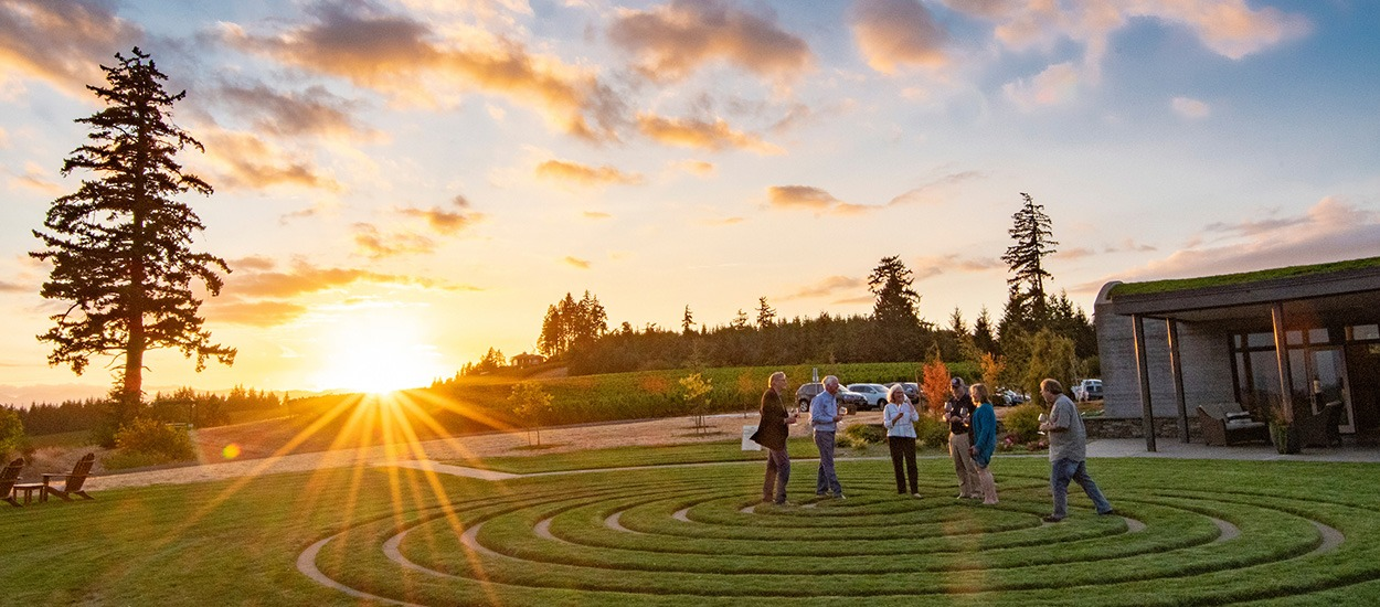 Fairsing Vineyard club members gather in the meditative labyrinth outside the tasting room as the sun sets over the Coastal range