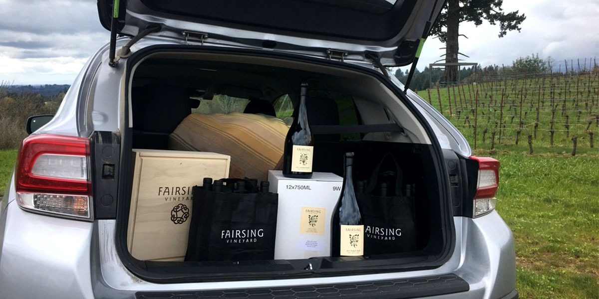 An open car trunk reveals Fairsing Vineyard wines loaded during curbside service at the winery in Oregon's Willamette Valley.