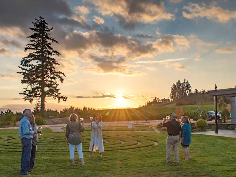 Guest enjoy Fairsing Vineyard estate wines at sunset near the tasting room and meditative labyrinth